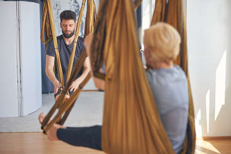 Two barefoot Caucasian people practicing aerial yoga