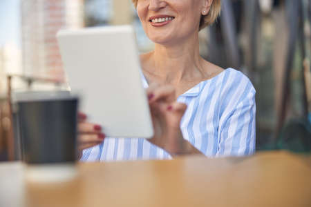 Joyful lady using her tablet computer outside 免版税图像