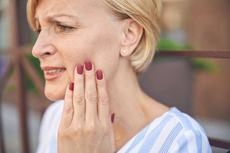 Low-spirited short-haired lady experiencing an acute toothache Standard-Bild