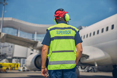 Airport worker looking at a parked plane