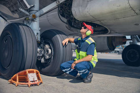 Qualified young technician inspecting the undercarriage axle