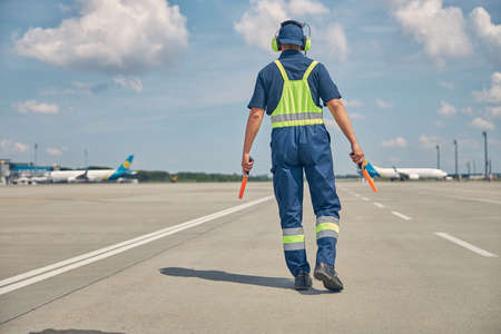 Signalman with wands going along the runway