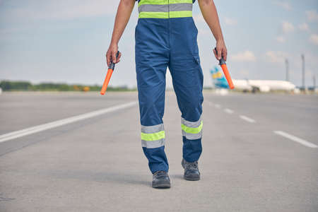 Signalman in workwear walking across the runway