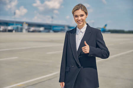 Smiling female airport worker on the runway
