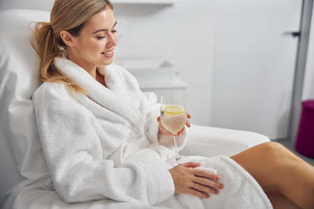 Joyful young woman with drink relaxing in spa salon