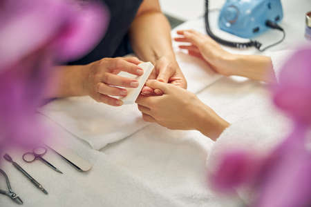 Nail artist doing manicure behind pink flowers