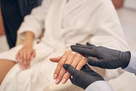 Beauty specialist applying body lotion on woman skin