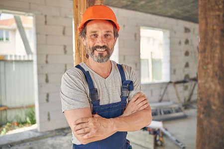 Joyful mature builder inside a half-finished house