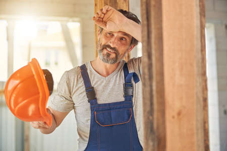 Smiling man in overalls holding his helmet