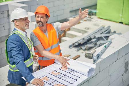 Smiling senior man listening to a builder