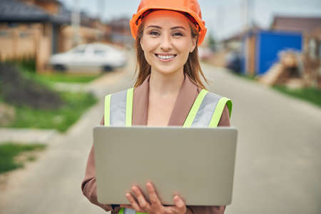 Cheerful lady in a protective helmet holding a laptop