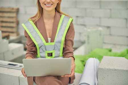 Cheerful woman in a reflective vest sitting outside Standard-Bild