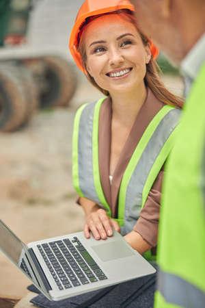 Contented blonde female worker holding her computer Standard-Bild