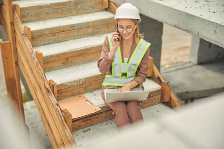 Businesswoman with a laptop sitting on the steps