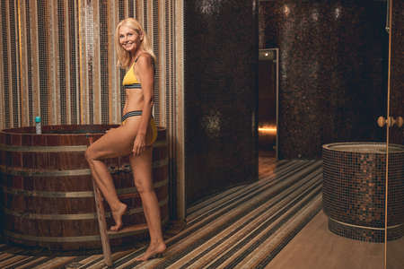 Happy cheerful lady in swimsuit having fine time to relax in spa Reklamní fotografie