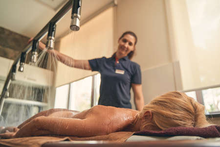 Woman lying on the wooden desk while taking the spa procedure Reklamní fotografie