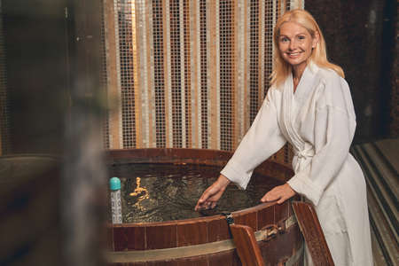 Laughing woman in white bathrobe standing at the barrel Reklamní fotografie