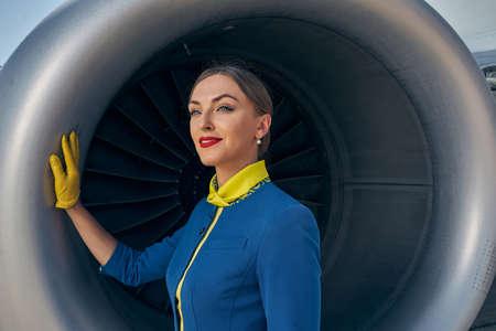 Serene elegant female flight attendant gazing away
