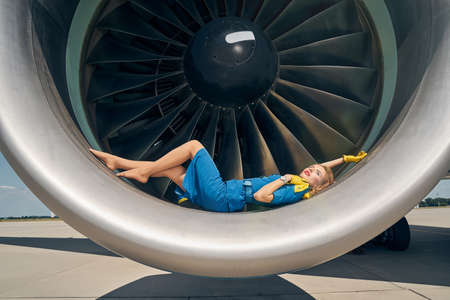 Lovely young daydreaming airline employee looking up