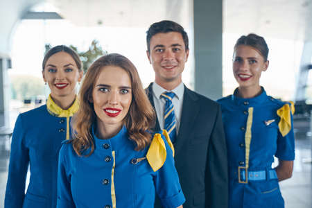 Handsome steward and female flight attendants looking forward