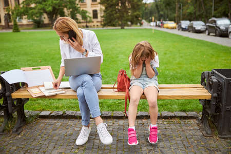 Hard working woman with laptop and mobile and her female child needing attention