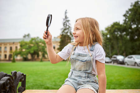 Happy smiling girl spending education time in the outdoors with lens