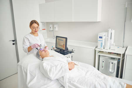 Smiling cosmetician treating her client with a photo beauty device