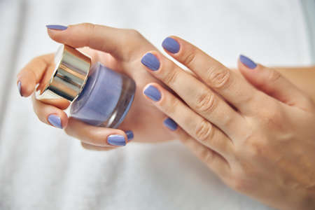 Woman with bottle of blue gel polish