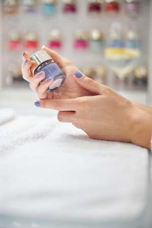 Lady doing bright manicure in beauty salon