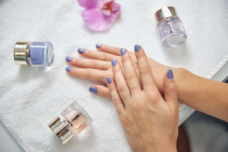 Woman after finishing professional fashionable manicure in salon