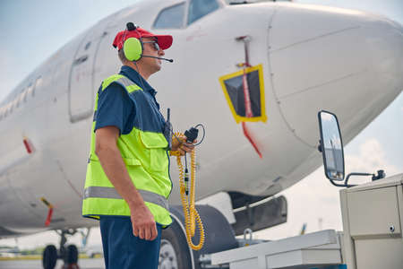 Man in headset standing by a pushback tractor