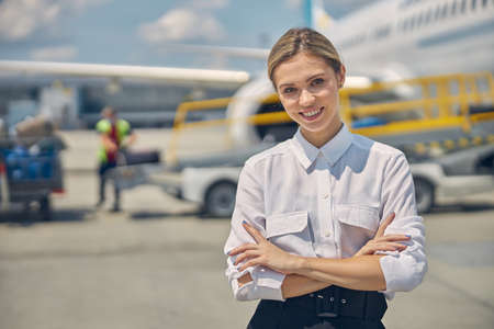 Smiling stylish airline employee is standing outdoors