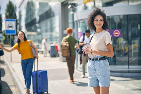Stylish woman in denim shorts and shirt with backpack on shoulder waiting for a taxi in the outdoors