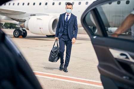 Young enterpreneur travelling safely with a mask on