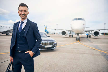 Successful businessman posing with a plane in the background Standard-Bild