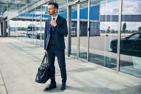 Weary-looking man exits the airport with his bag