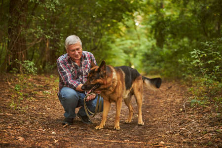 Senior man sitting on his haunches next to a dog