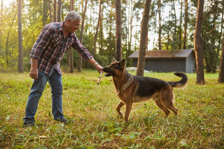 Happy senior citizen playing with his dog outside