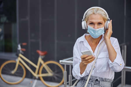 Gorgeous woman with mobile and headphones resting in the empty place of city