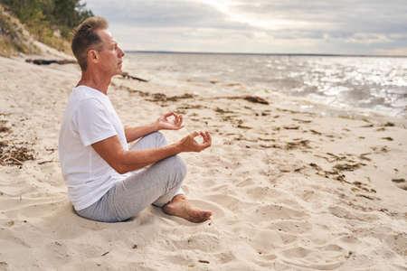 Mature man meditating in morning in beach