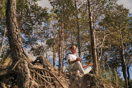 Calm man doing meditation in green forest