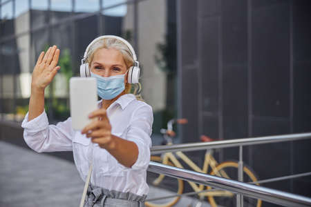 Happy blonde Caucasian female holding white mobile phone in hand