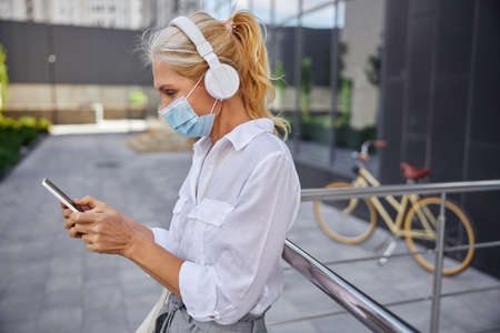 Stylish female using smartphone while spending time in the city street