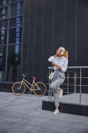 Business woman resting after hard working day in the empty space in front of modern building