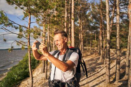 Merry man taking photo of beautiful scenery in nature