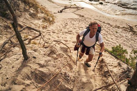 Athletic male going nordic walking near sea shore