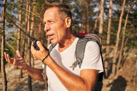 Man using walkie talkie while hiking in wood