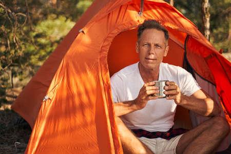 Happy man enjoying hot drink in tent