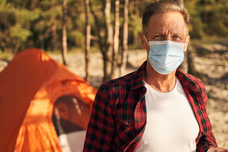 Mature man in medical mask going camping Archivio Fotografico