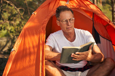 Mature man enjoying reading book in nature